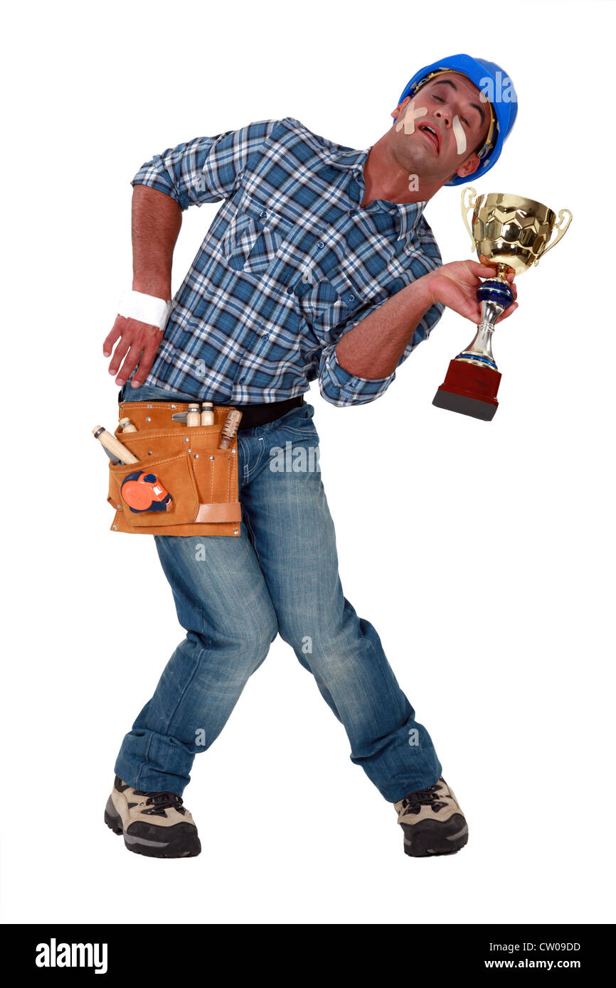 Accident prone construction worker holding a trophy - Stock Image