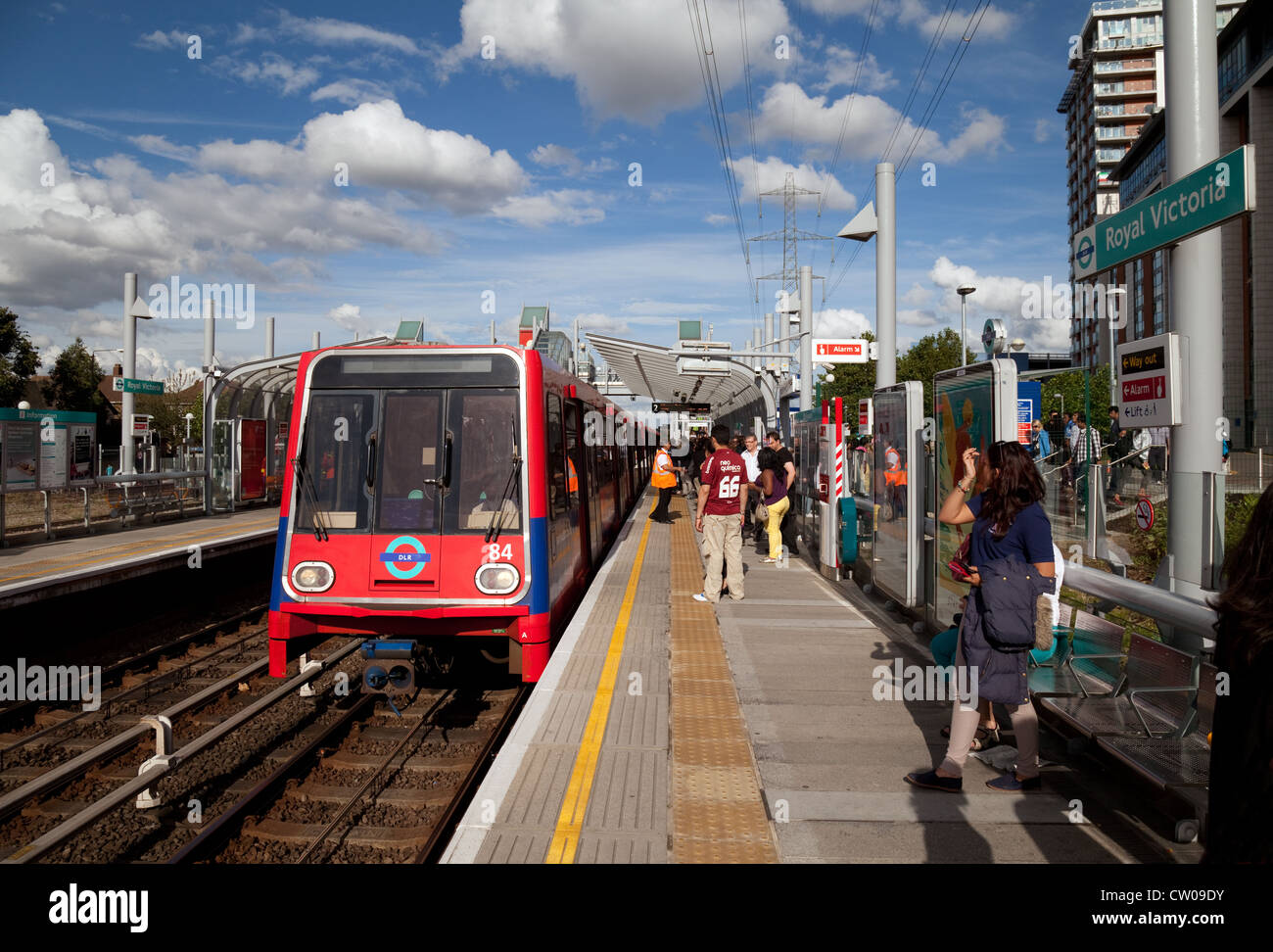 Passengers and a train at the DLR (Docklands Light Railway) station at Royal Victoria, London UK - Stock Image