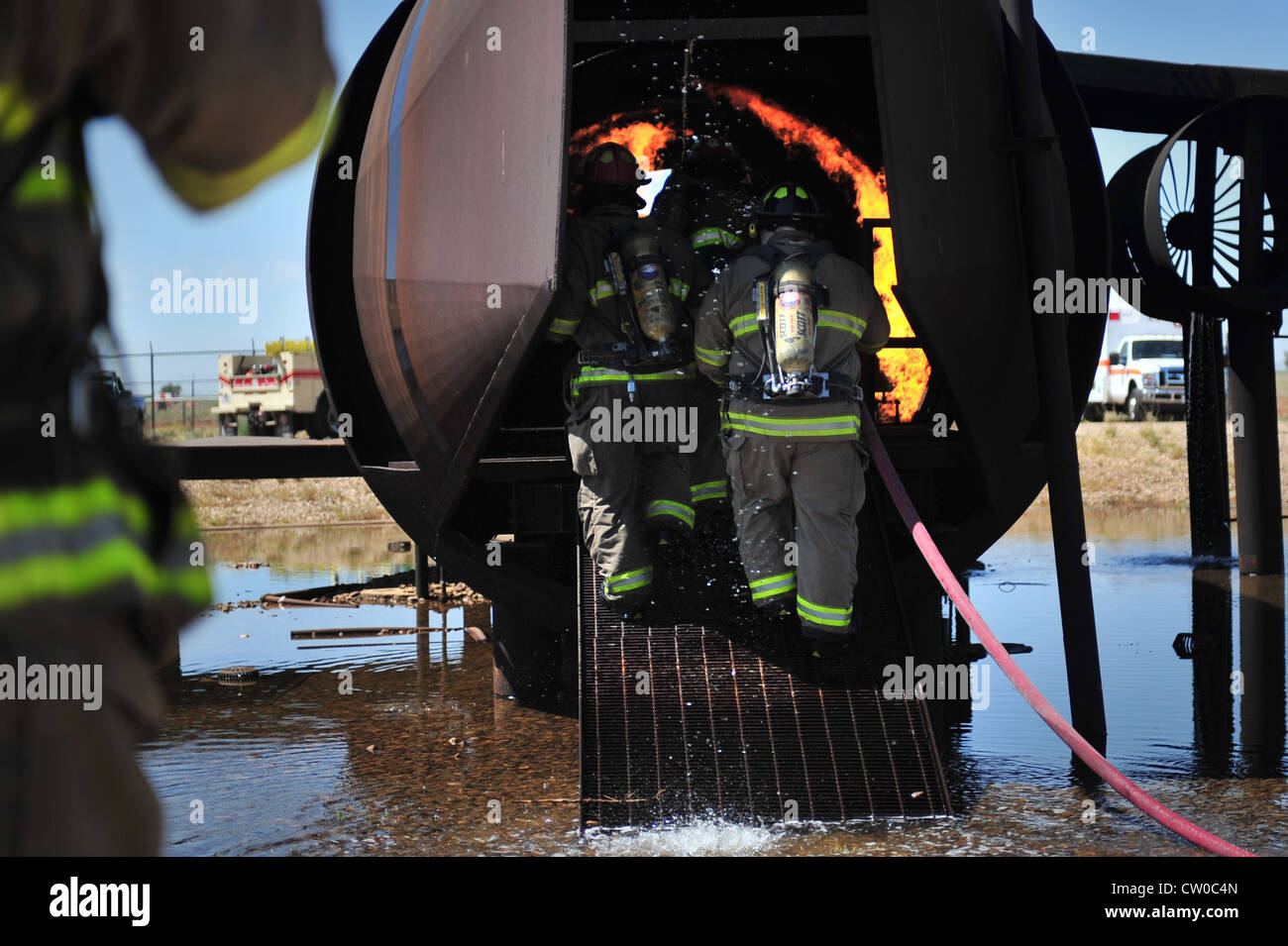 Firefighters with the Clovis, N.M. Fire Department enter the burn pit aircraft to extinguish a fire at Cannon Air - Stock Image