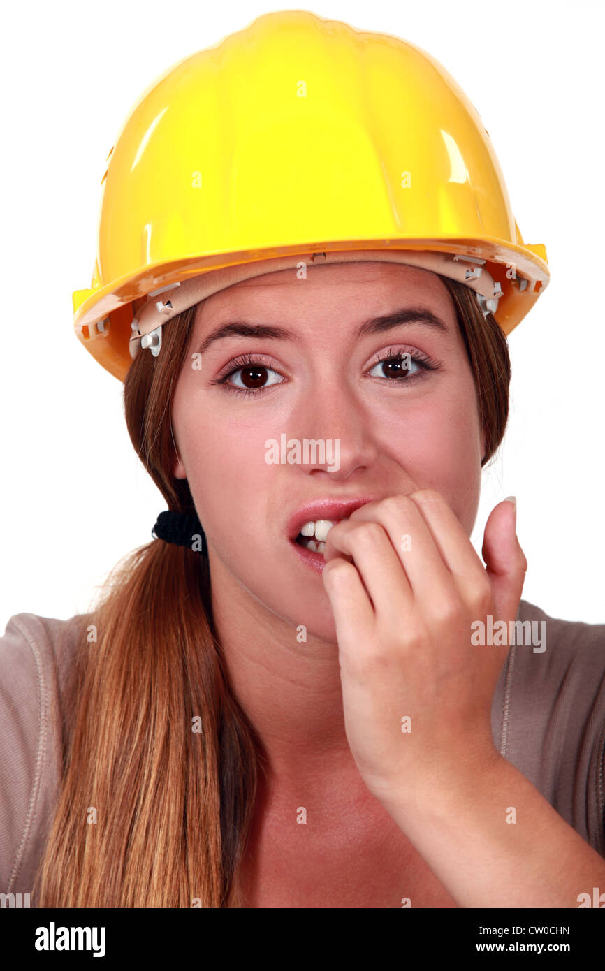 Woman with helmet biting her nails - Stock Image