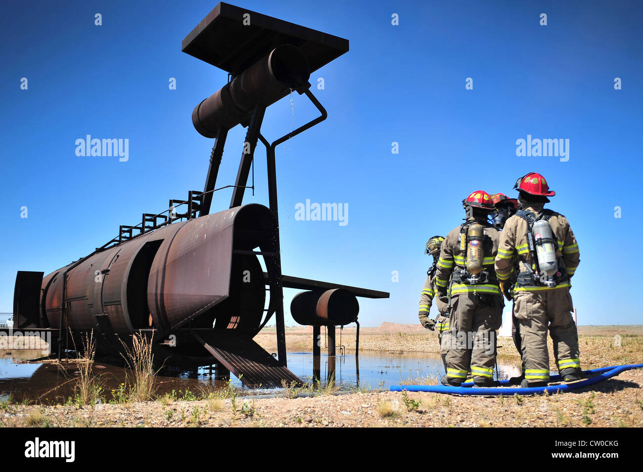 Members of the Clovis, N.M., Fire Department prepare to enter the burn pit to extinguish a fire at Cannon Air Force - Stock Image