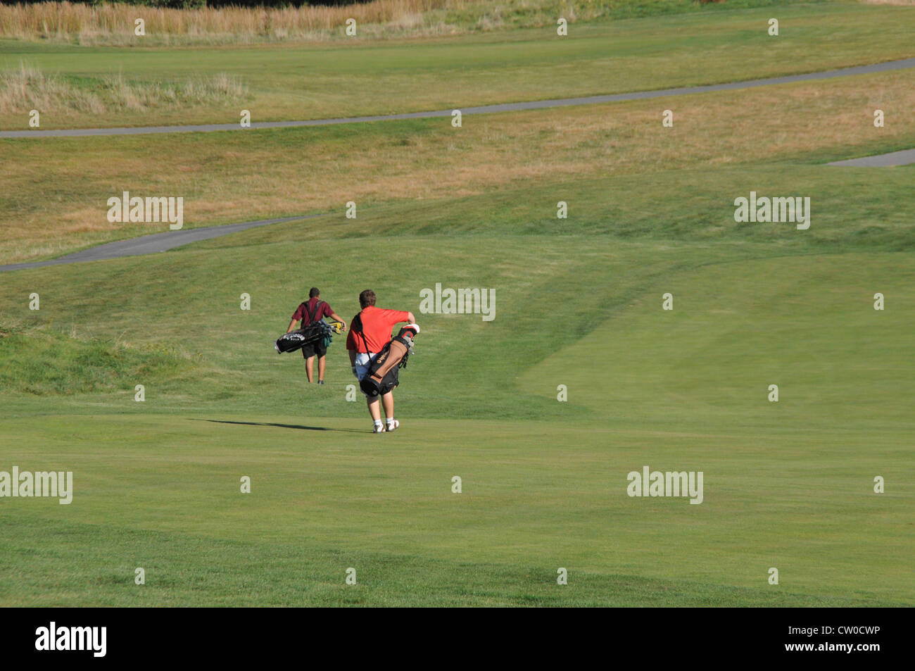 teen golfers walking to the next hole - Stock Image