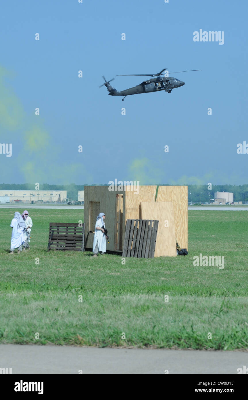 Mock adversaries scramble as a UH-60 Blackhawk approaches the Campbell Army Airfield Tuesday. This demonstration - Stock Image