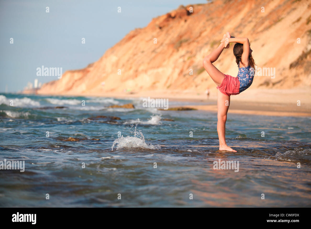 Woman practicing yoga on beach - Stock Image
