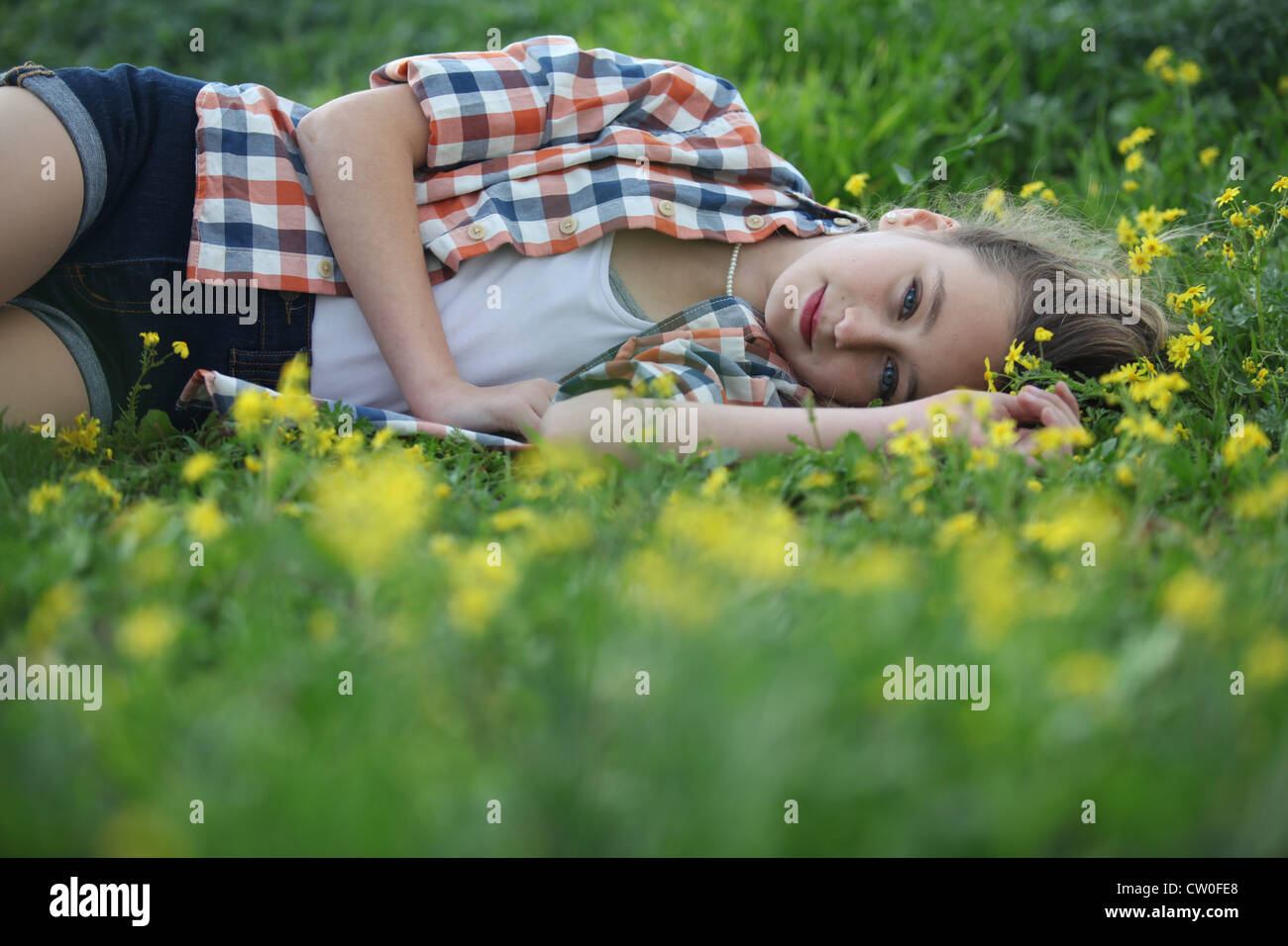 Woman laying in field of flowers Stock Photo