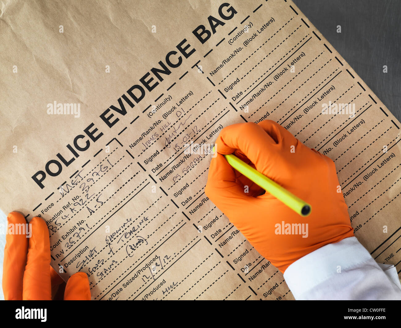 Scientist filling out evidence bag - Stock Image