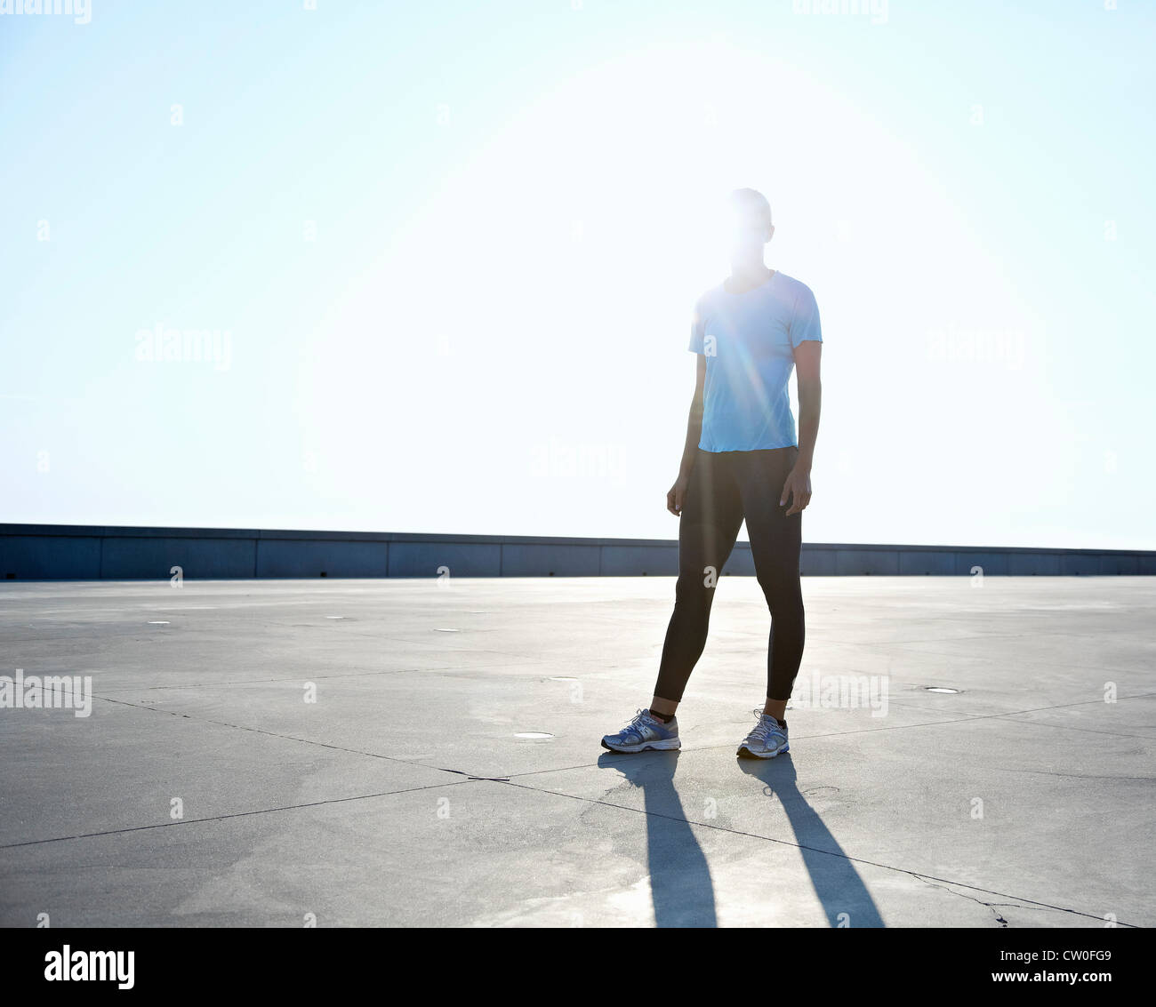 Runner standing on rooftop - Stock Image