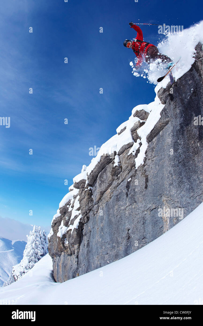Skier jumping on rocky slope - Stock Image