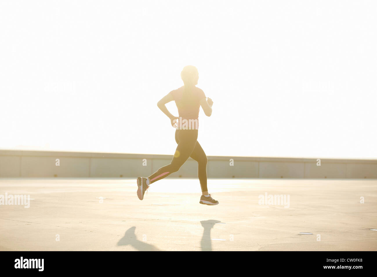 Man running on rooftop - Stock Image