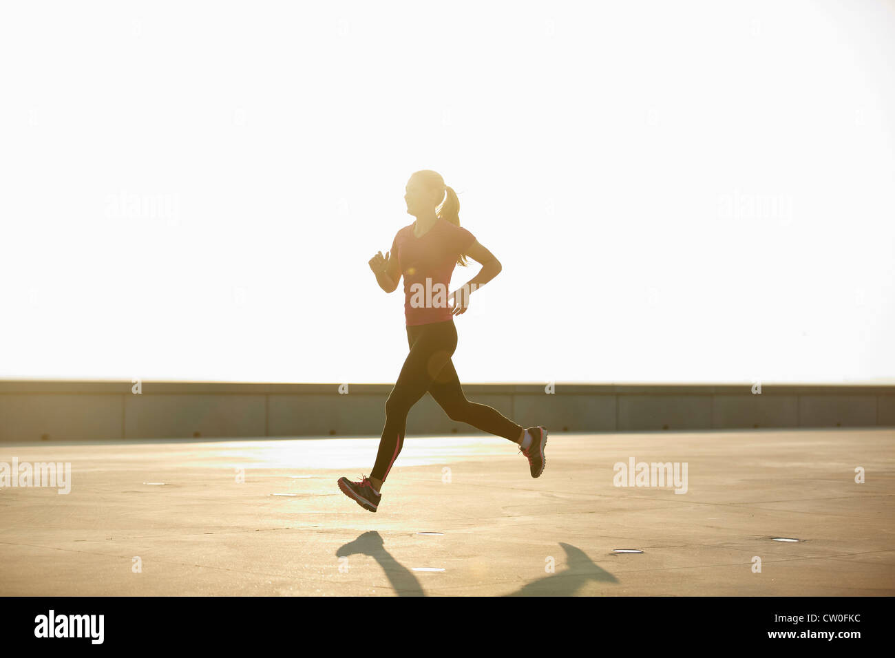 Woman running on rooftop - Stock Image