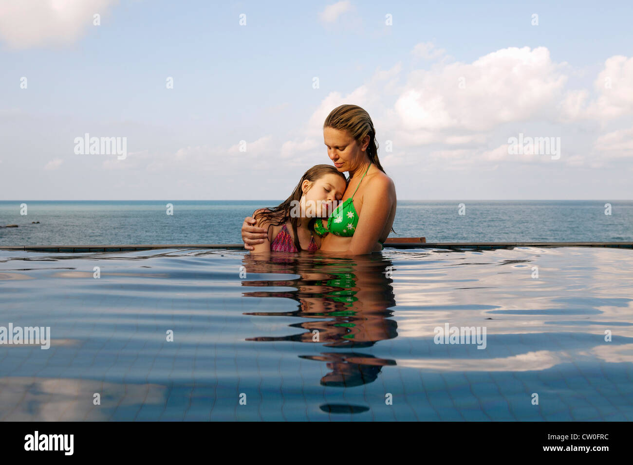 Mother and daughter in infinity pool - Stock Image