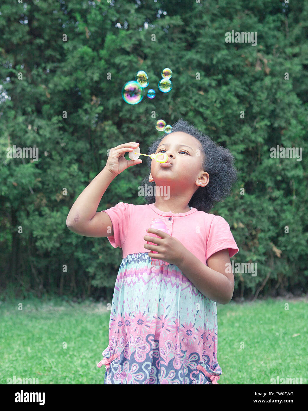 Girl blowing bubbles outdoors - Stock Image