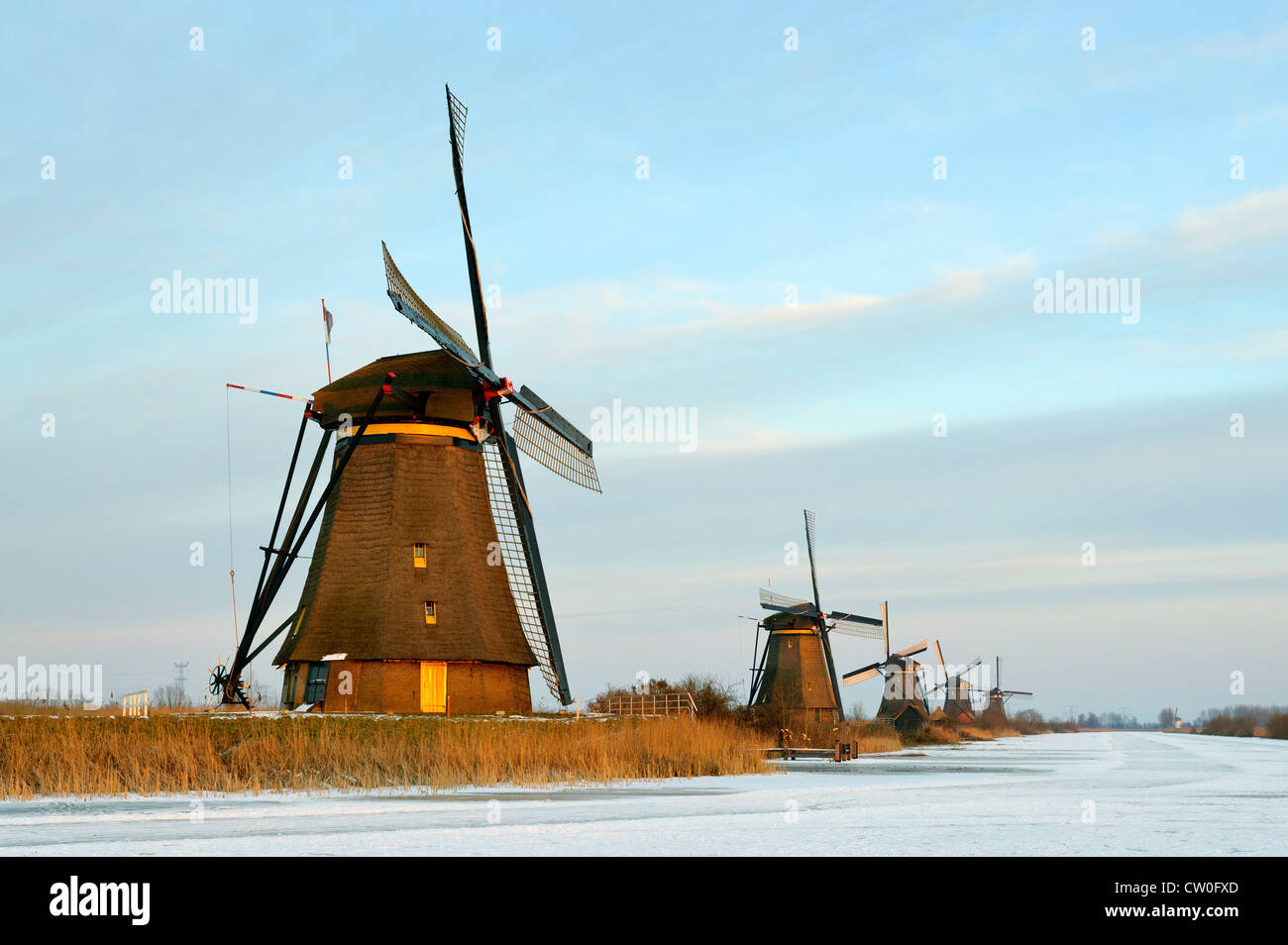 Windmills by frozen rural lake - Stock Image