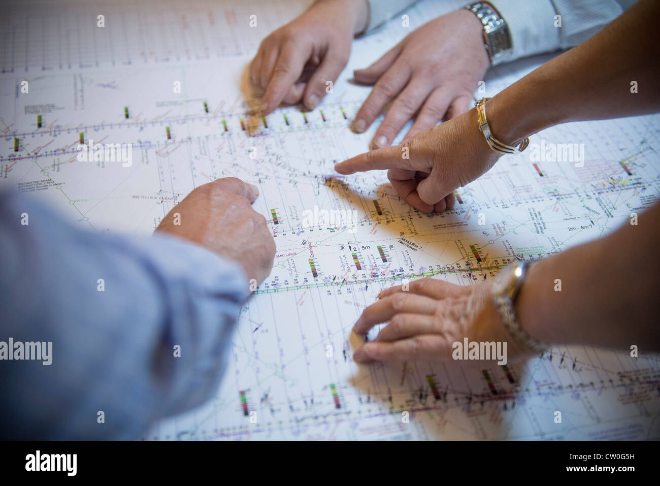 Business people reading coal mine plans - Stock Image