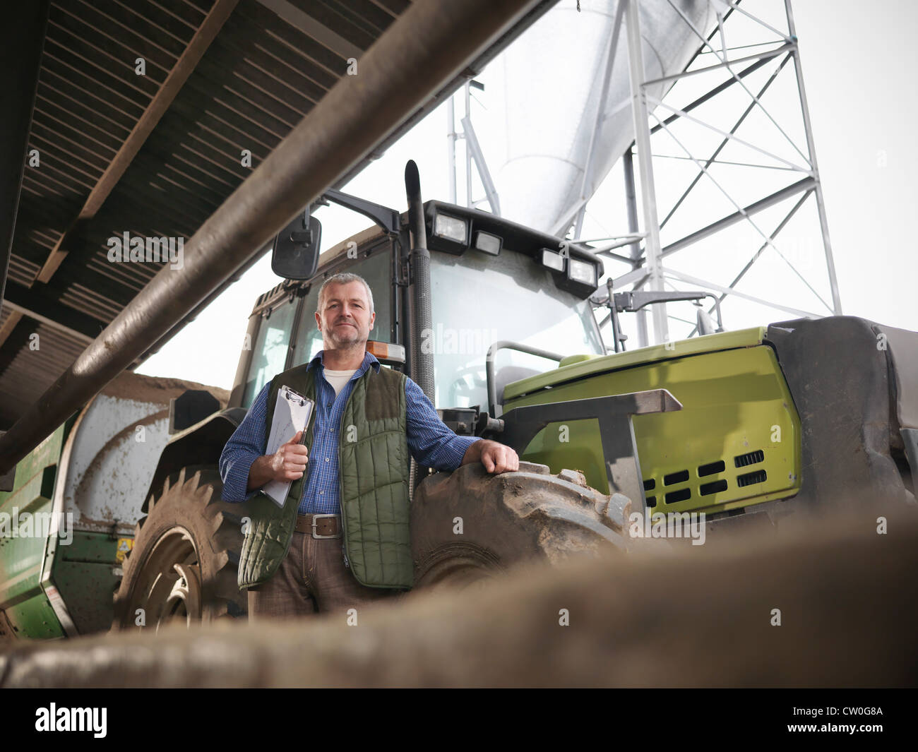 Farmer holding clipboard by tractor - Stock Image