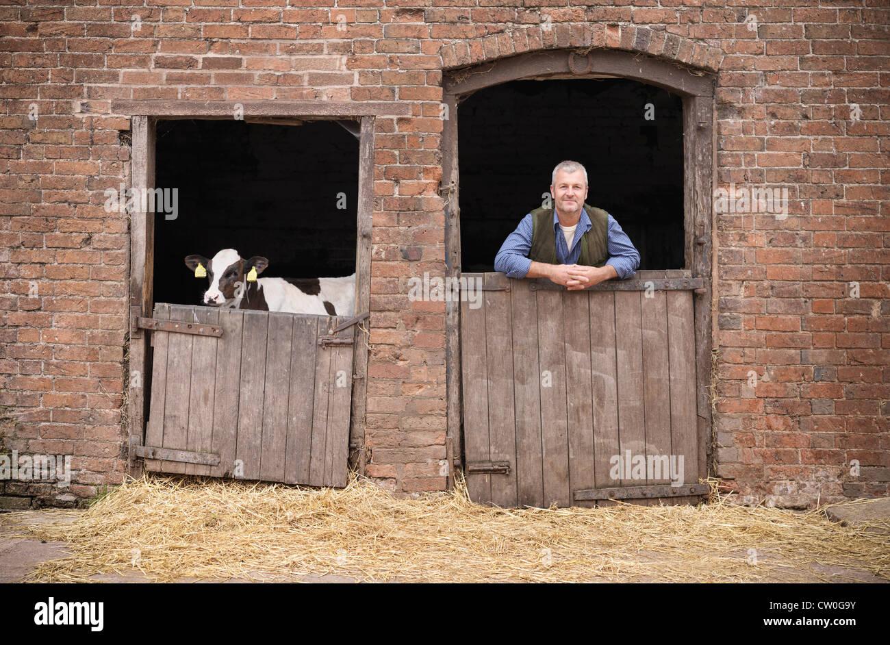 Farmer standing at gate of barn - Stock Image