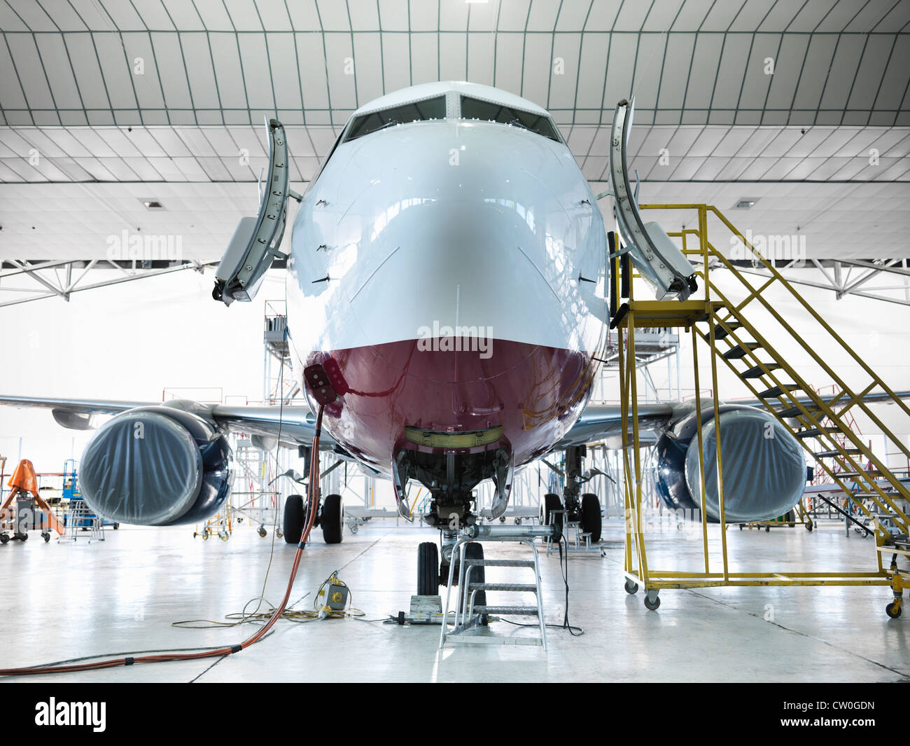 Airplane docked in hangar - Stock Image