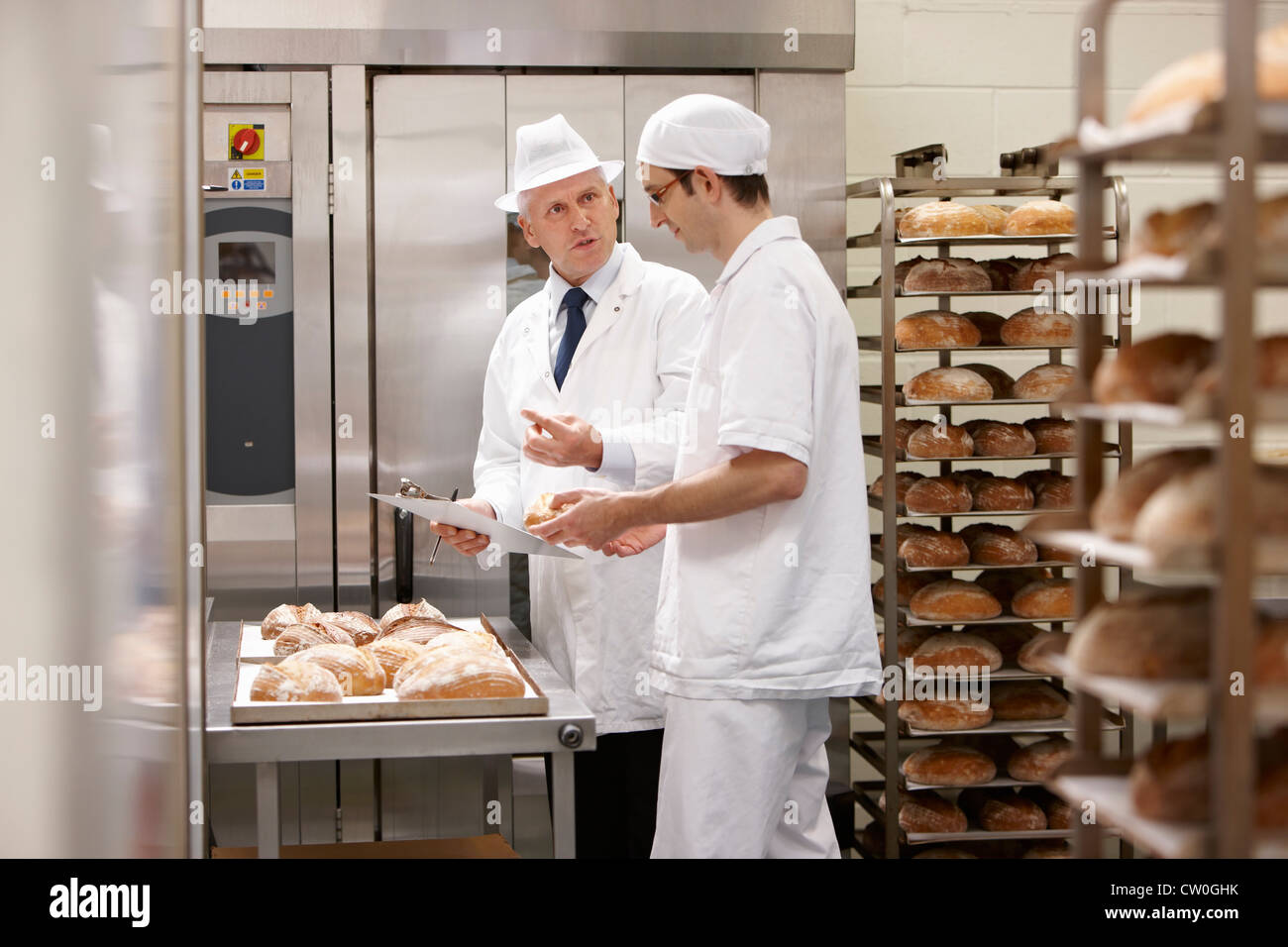 Health inspector with chef in kitchen - Stock Image