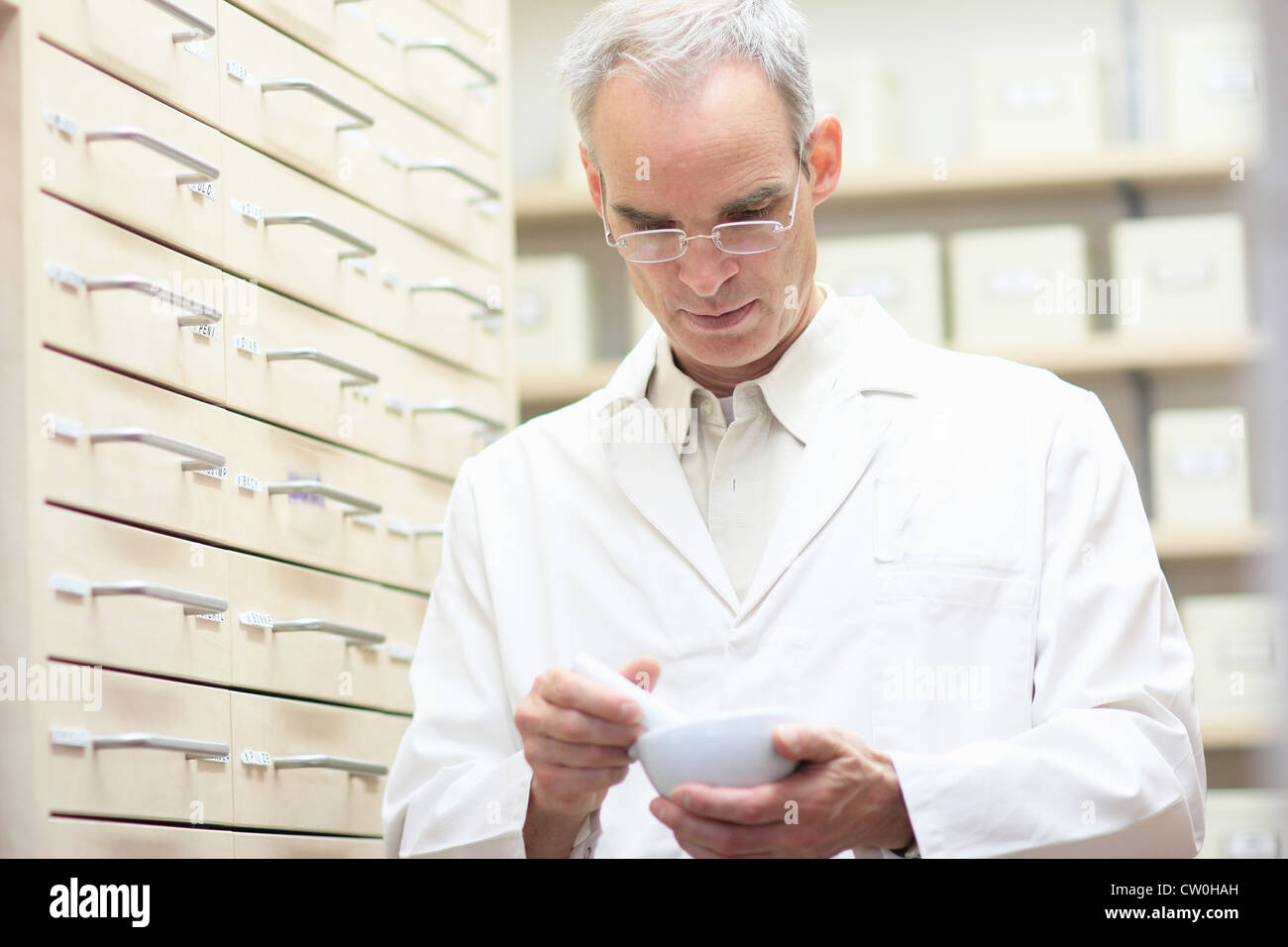 Pharmacist using pestle and mortar - Stock Image