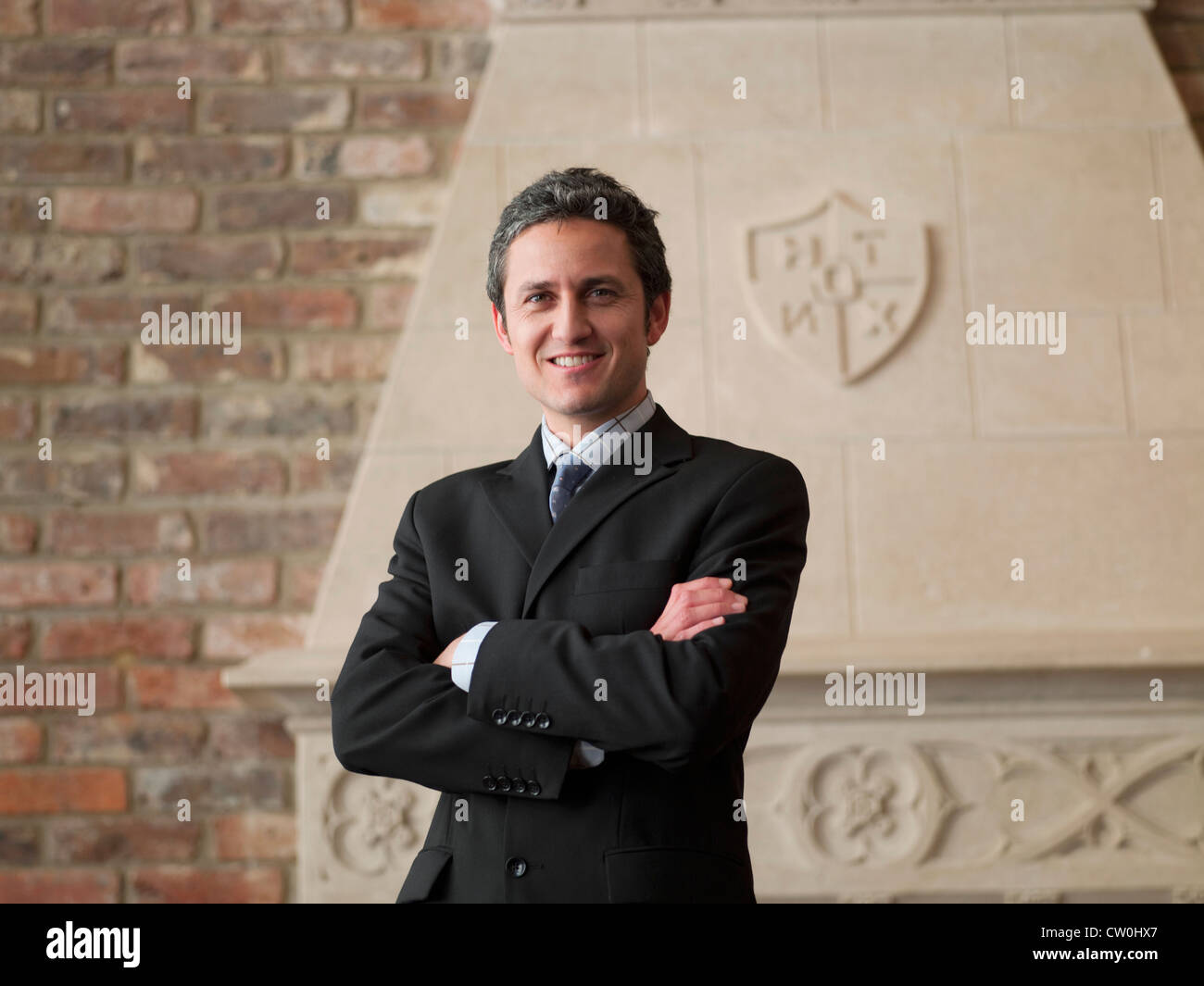Businessman standing with arms crossed - Stock Image