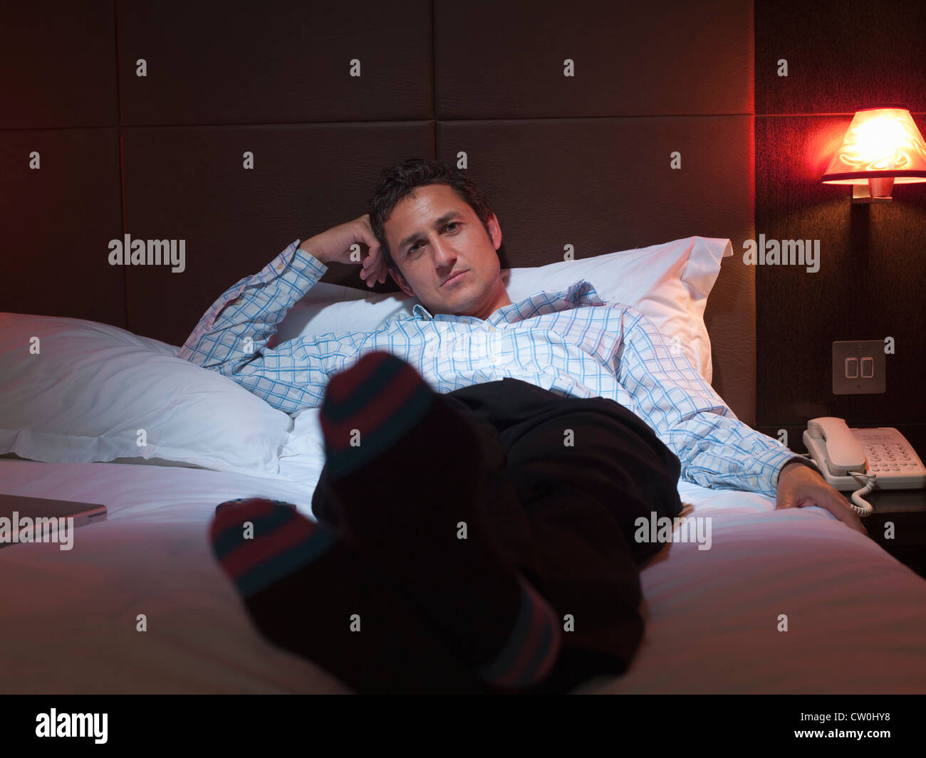 Businessman relaxing in hotel room - Stock Image
