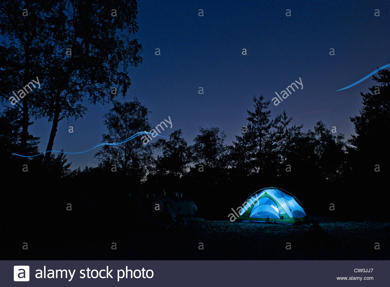Glowing lights in tent at campsite Stock Photo
