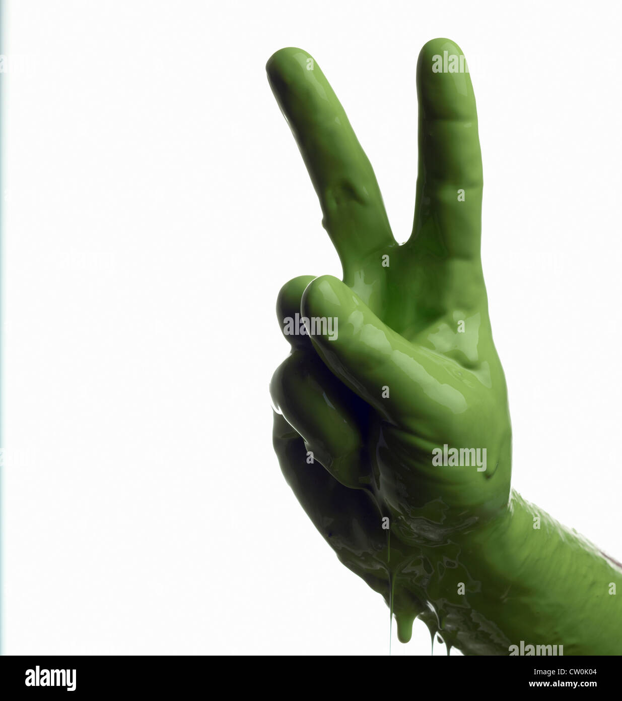 Green painted hand making peace sign - Stock Image