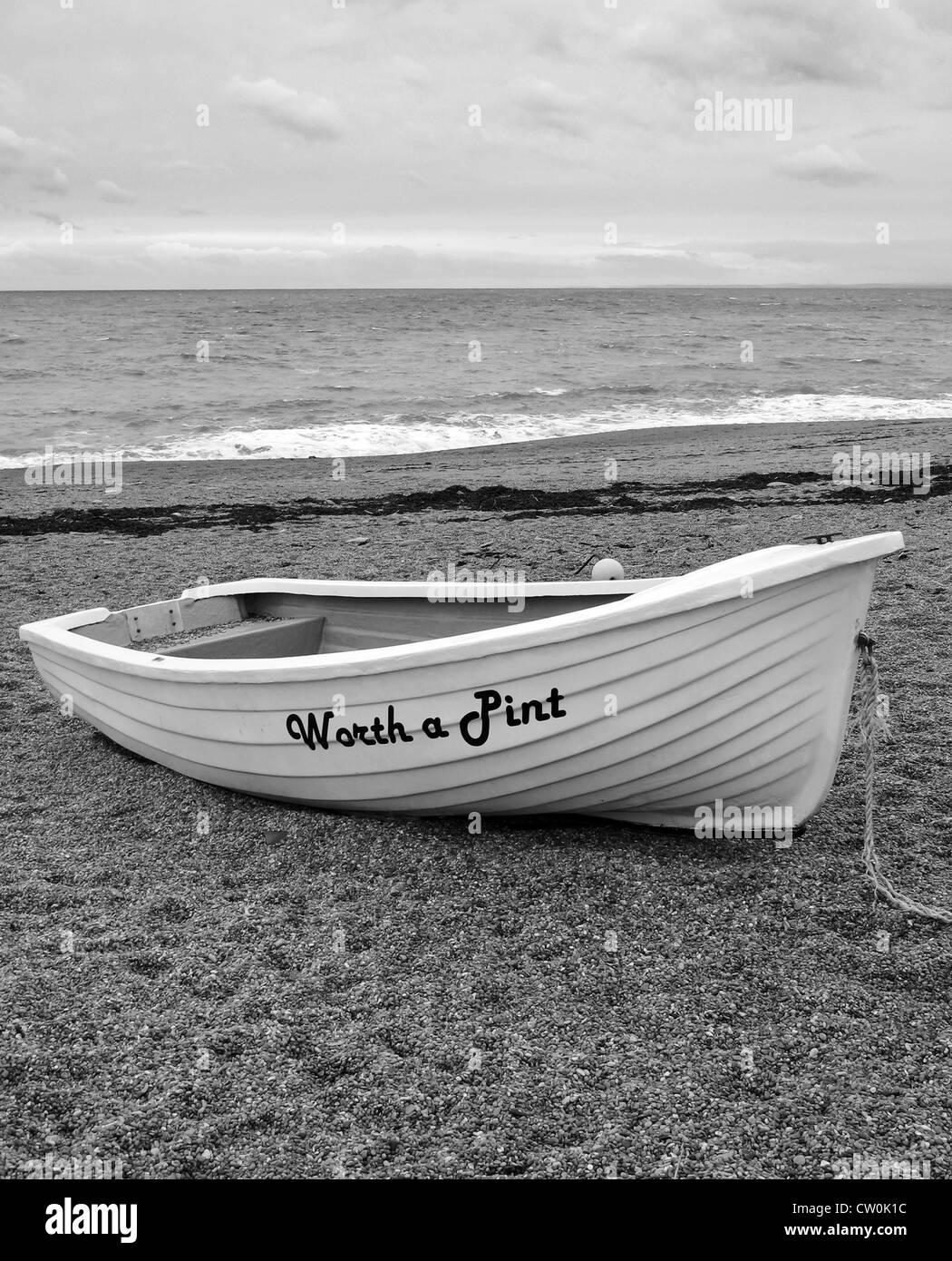 "Boat ""Worth a Pint"" on Burton Bradstock beach, Dorset, UK - Stock Image"