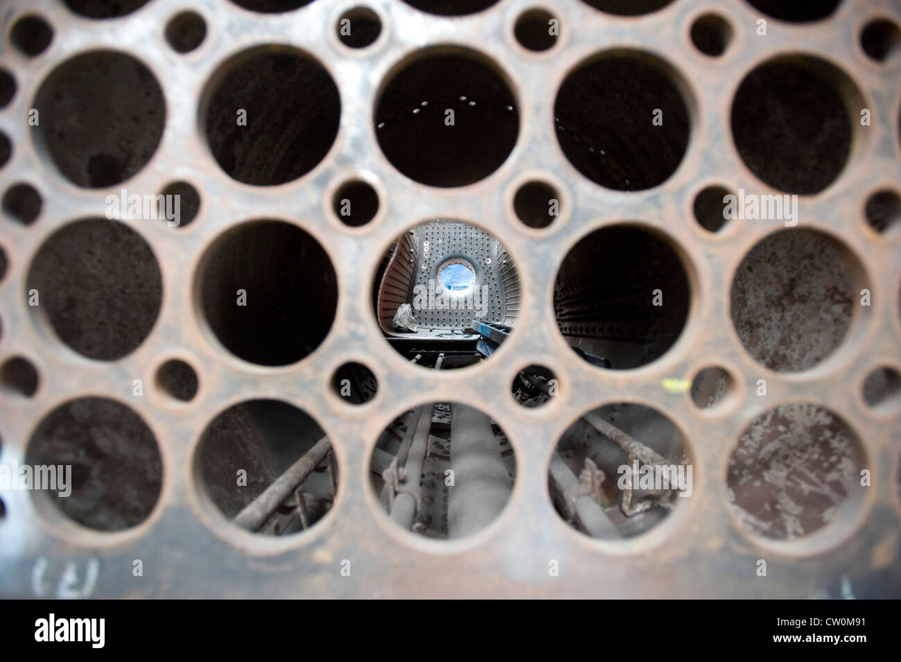 A steam engine boiler seen through the tube holes during restoration at  Mid Hants Railway, Watercress Line,Ropley, - Stock Image