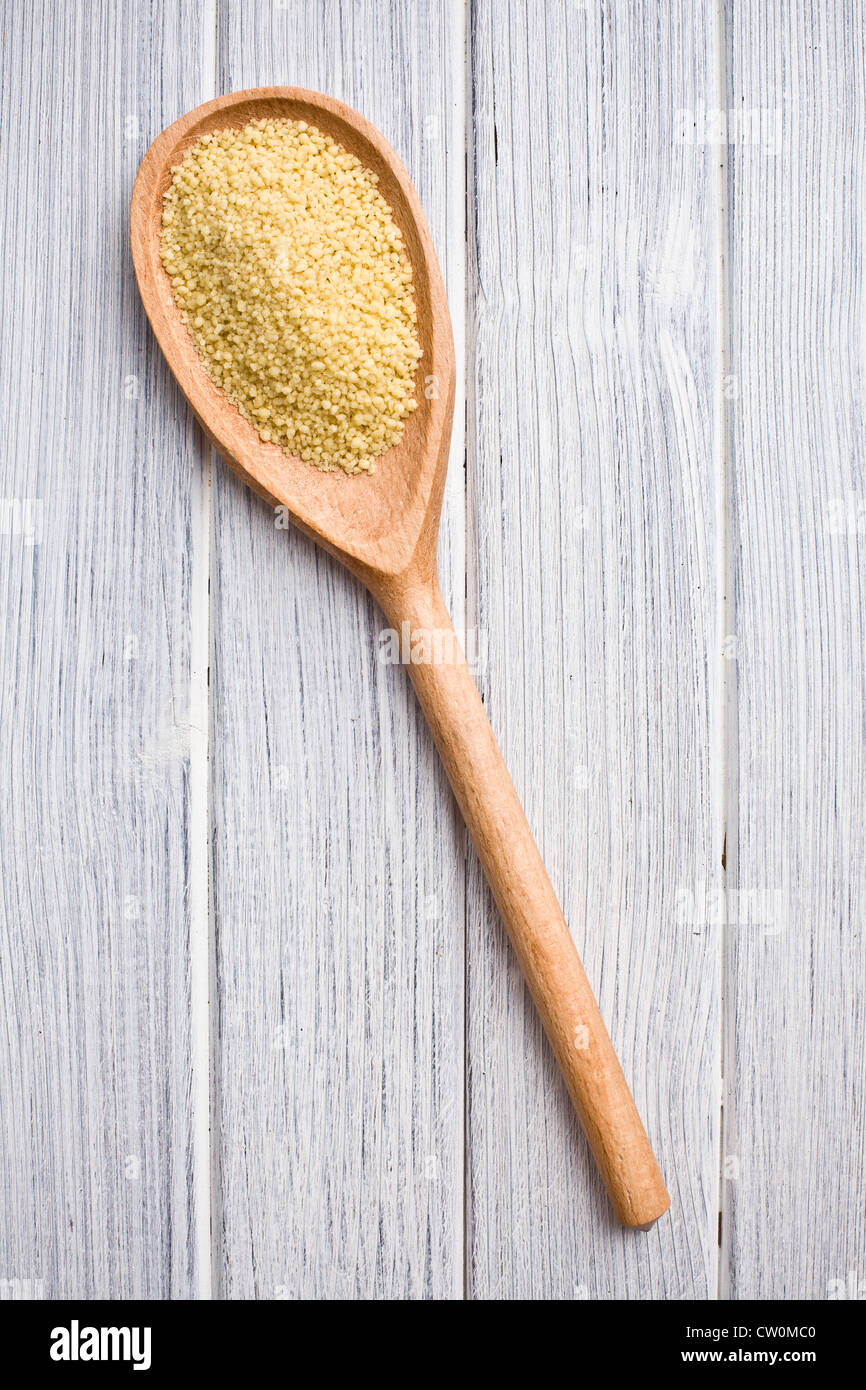 couscous in wooden spoon on kitchen table - Stock Image