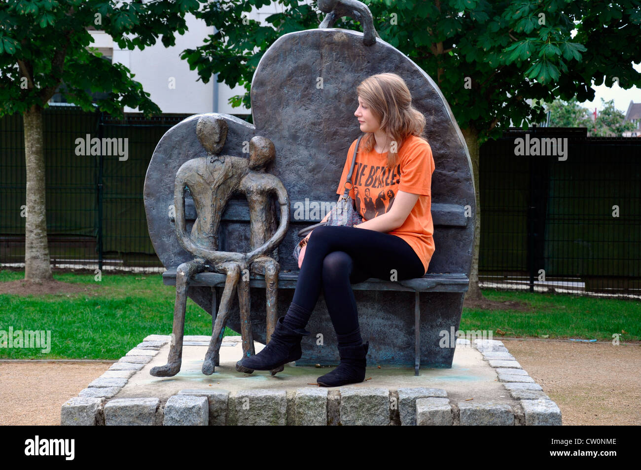 Pretty teenage girl sitting on a bronze loveseat, with a heart shaped back, in a public park in Neufchatel en Bray, - Stock Image