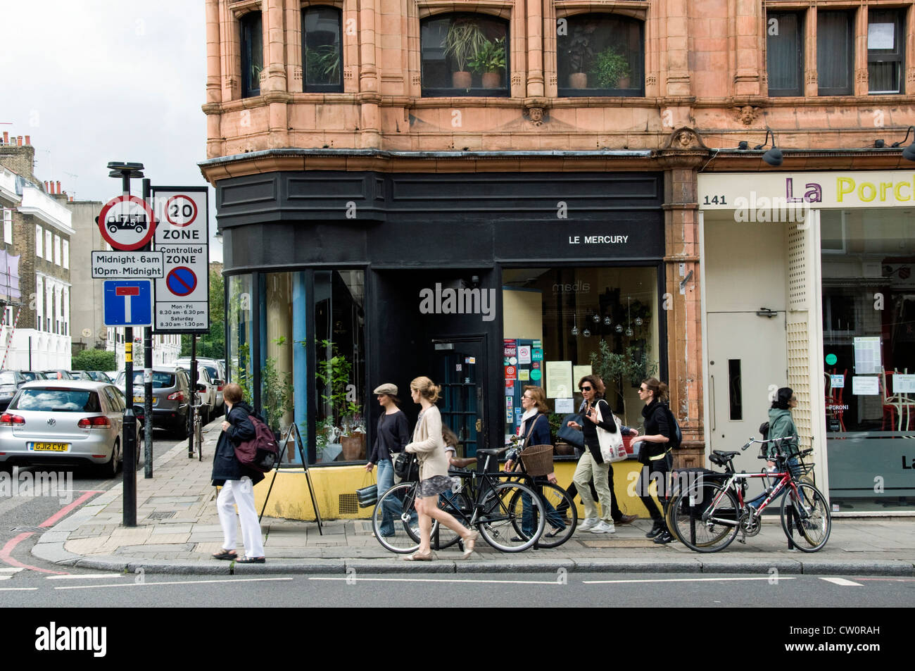 Busy street corner in front of Le Mercury resturant in Upper Street with people passing, Islington London England - Stock Image