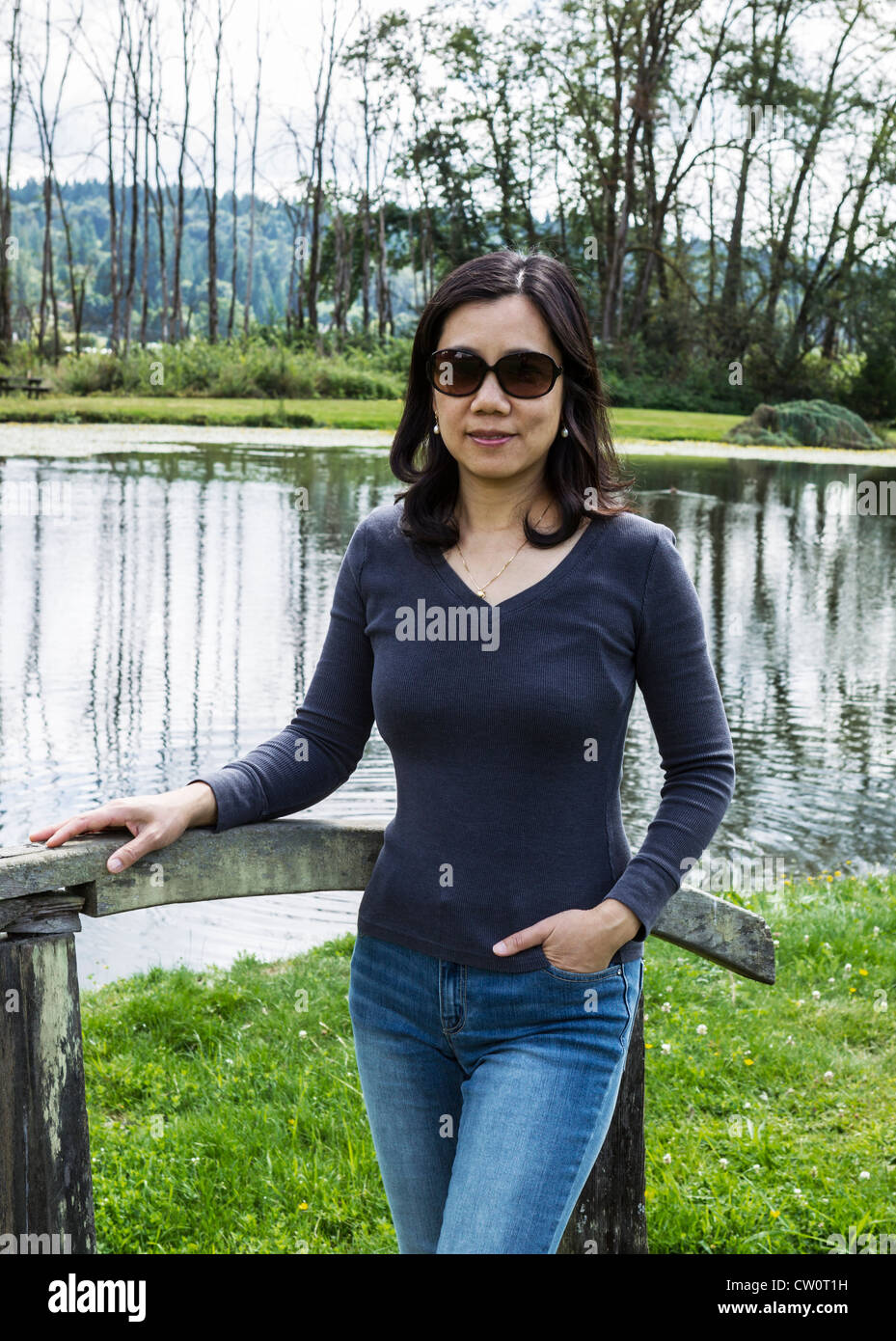 Mature Asian Women Standing On Wooden Bridge With Lake And -4854