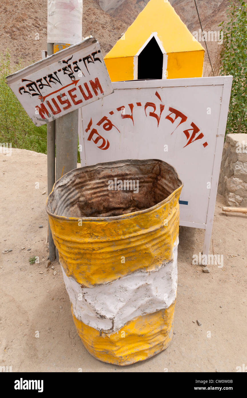 A very beat up yellow and white striped trash can at the Likir Monastery in Ladakh, India. Stock Photo