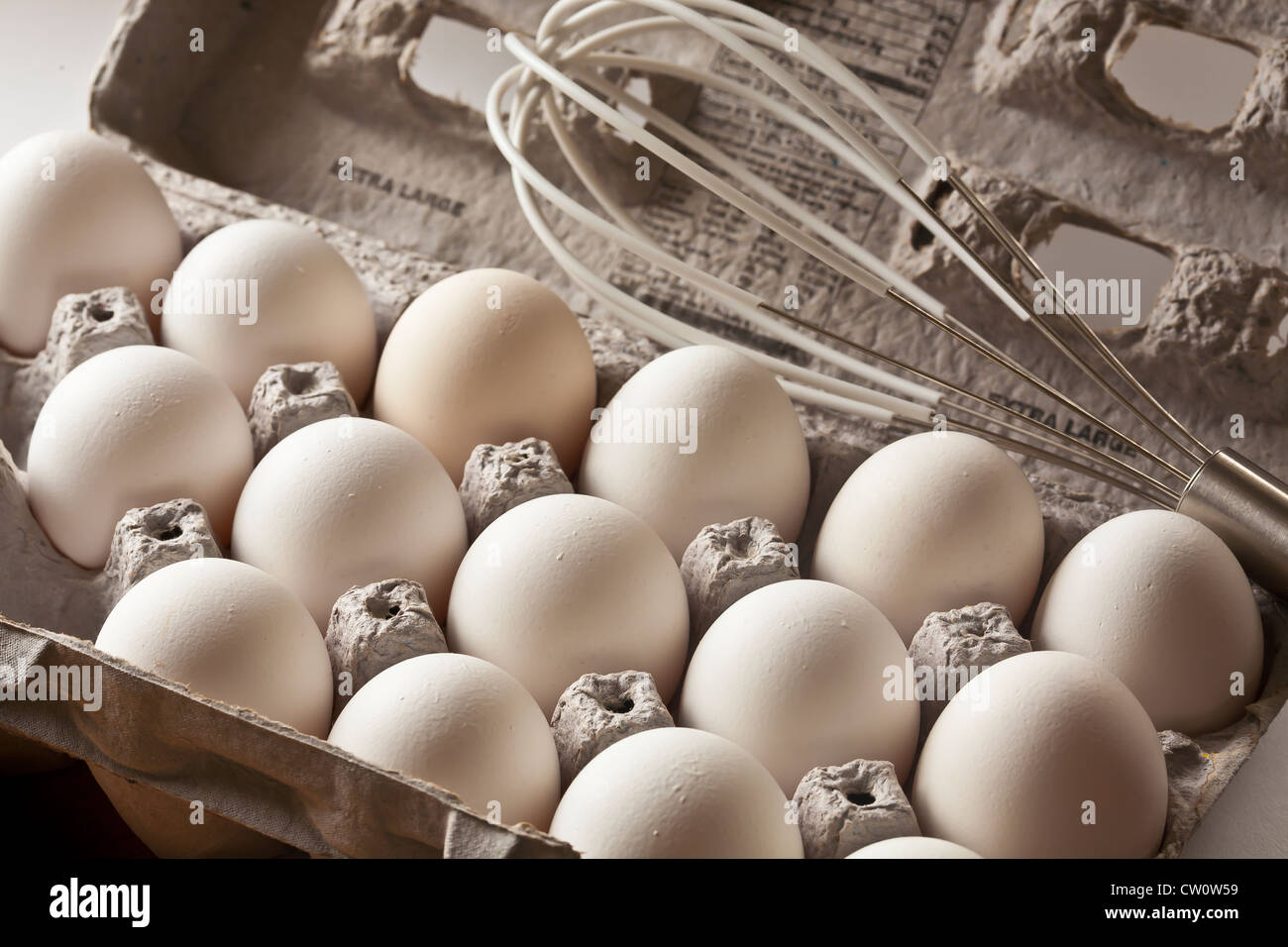 eggs in carton with stainless-steel wisk - Stock Image