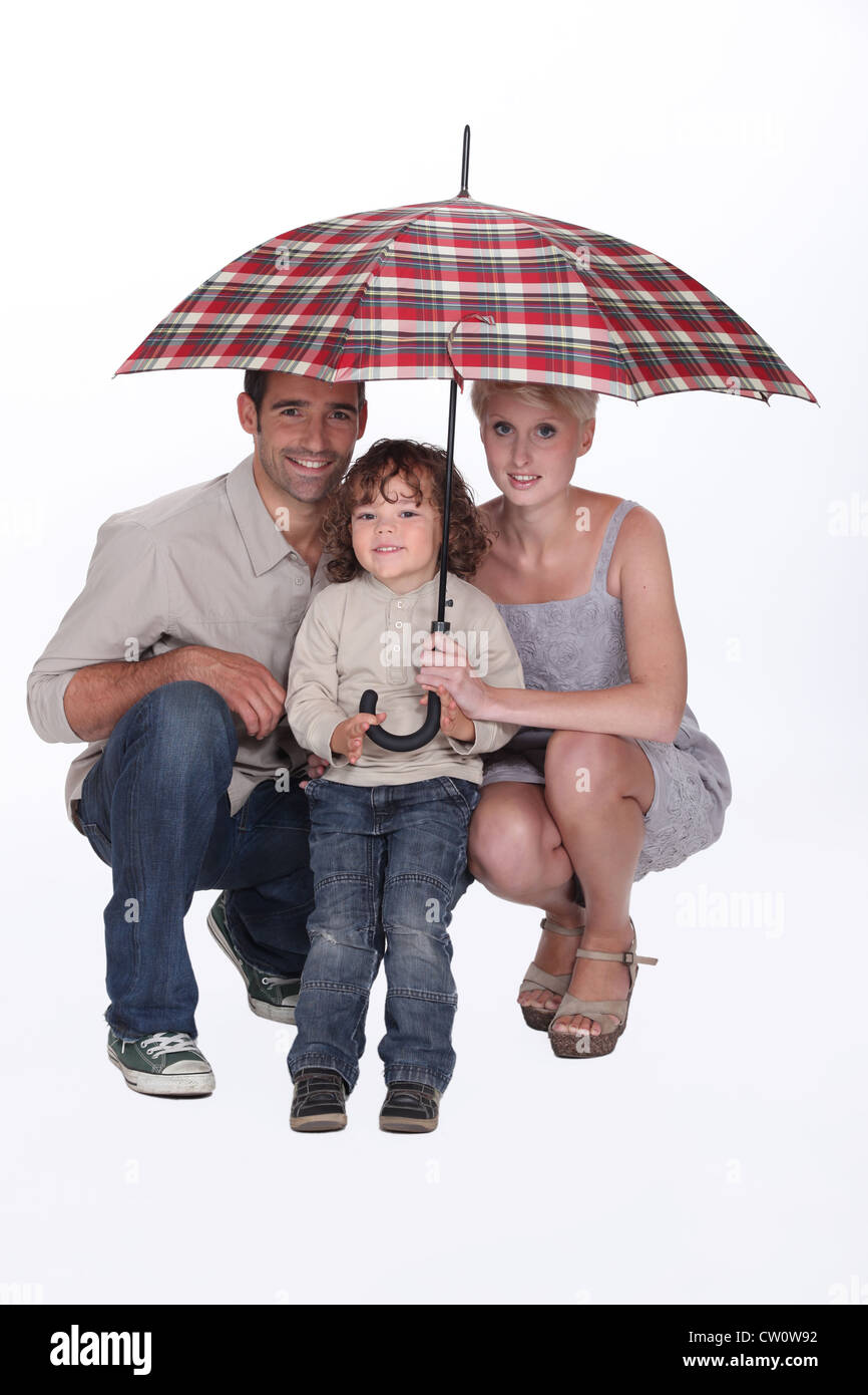 Young family crouching under an umbrella - Stock Image