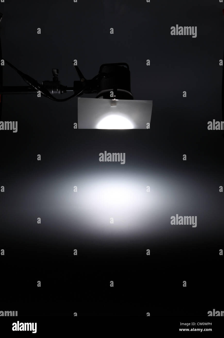 A photographic light from above creating a white spotlight on an empty dark background. - Stock Image