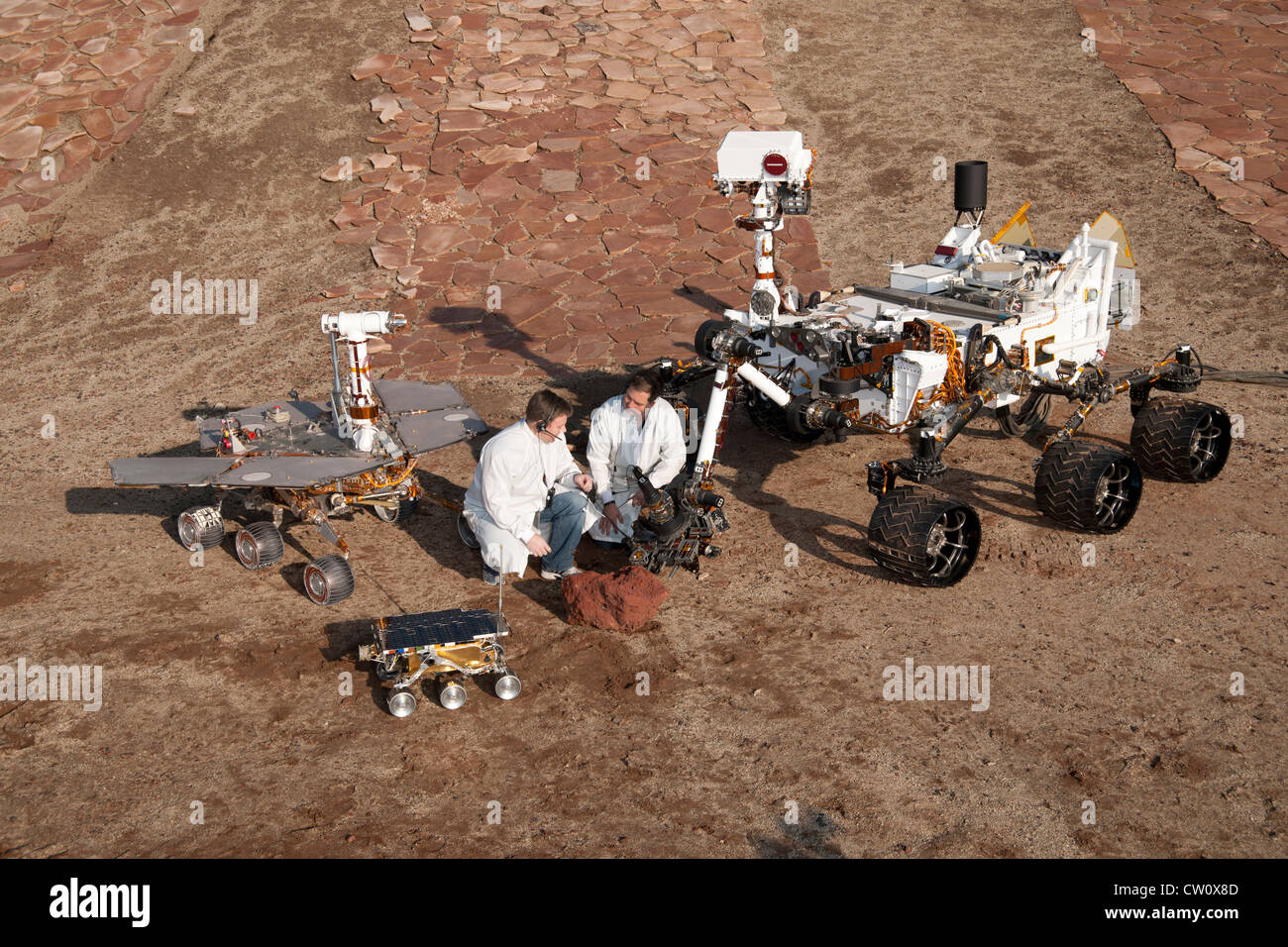 Two spacecraft engineers with Mars rovers: Sojourner, Mars Exploration Rover Project test rover and Curiosity - Stock Image