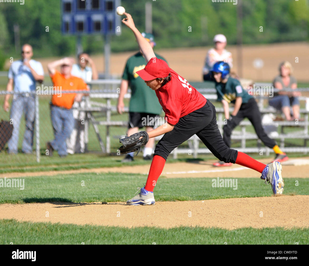 right handed little league baseball pitcher throwing the ball from the pitcher's mound - Stock Image