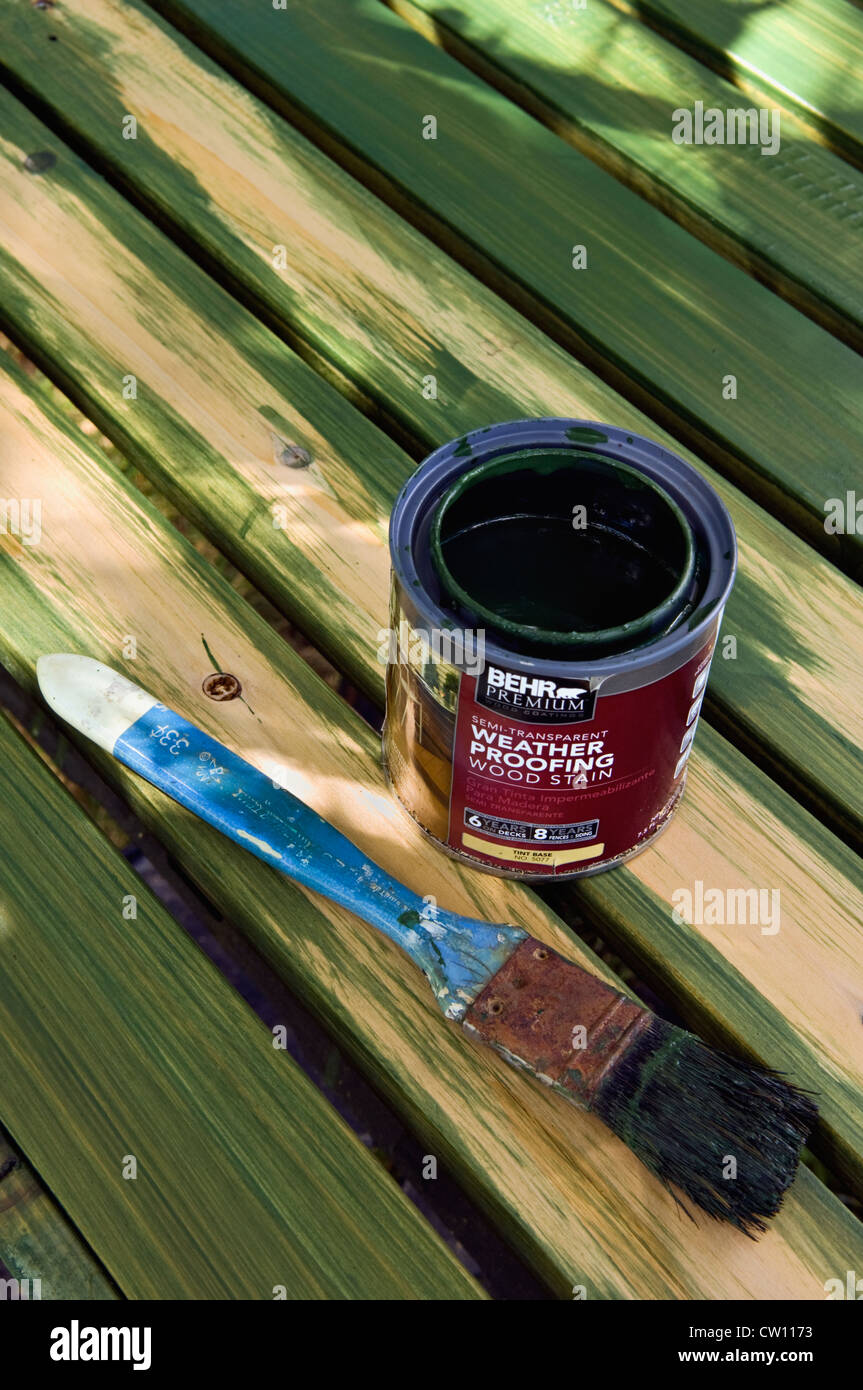 Open Can of Wood Stain and Wet Paint Brush on Partially Stained Wood - Stock Image