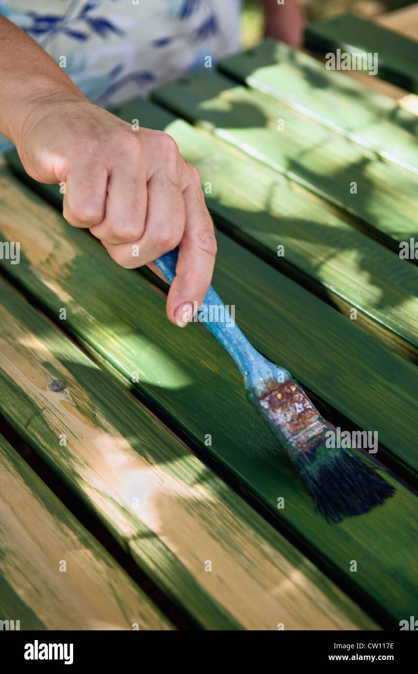 Close-up of a Adirondack Chair being Painted with Semi-transparent Wood Stain - Stock Image
