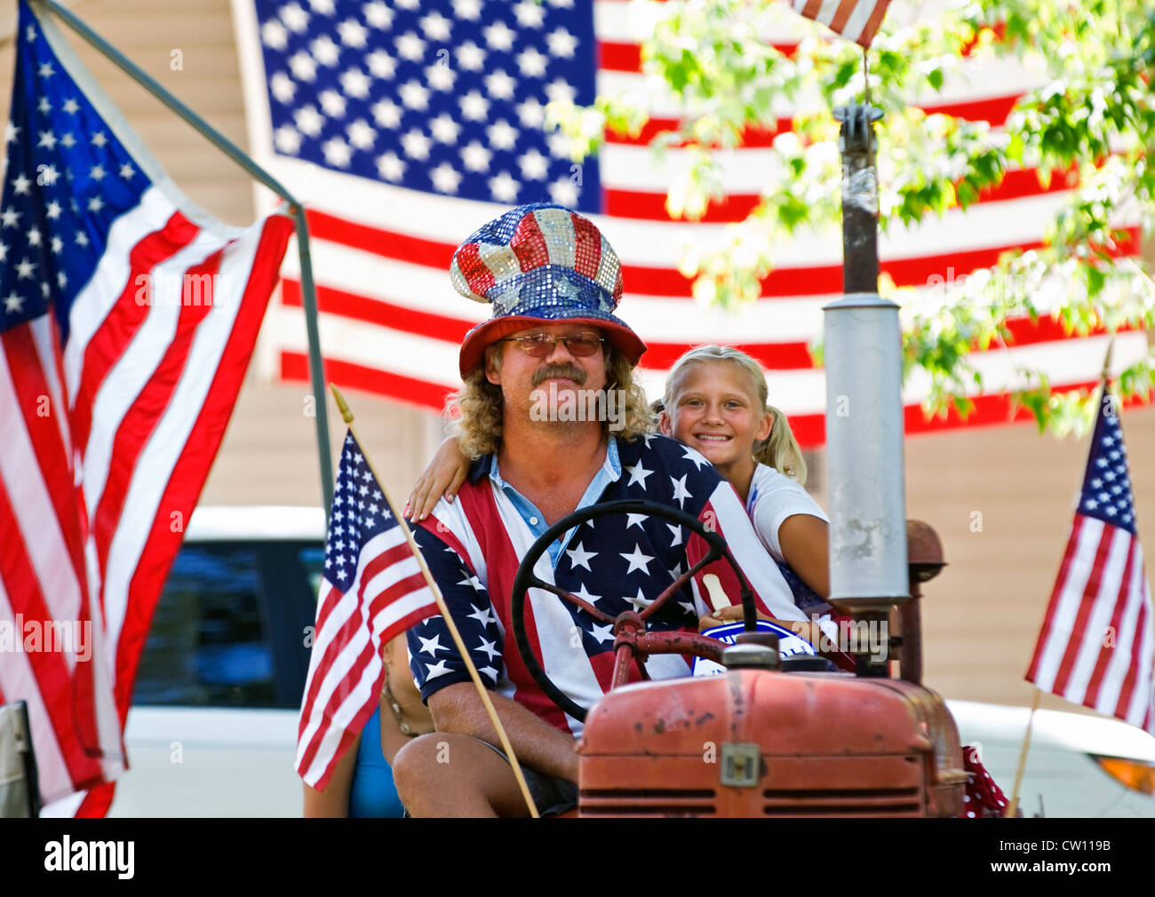 Patriotic Father and Daughter on Tractor after Independence Day Parade in New Pekin, Indiana Stock Photo