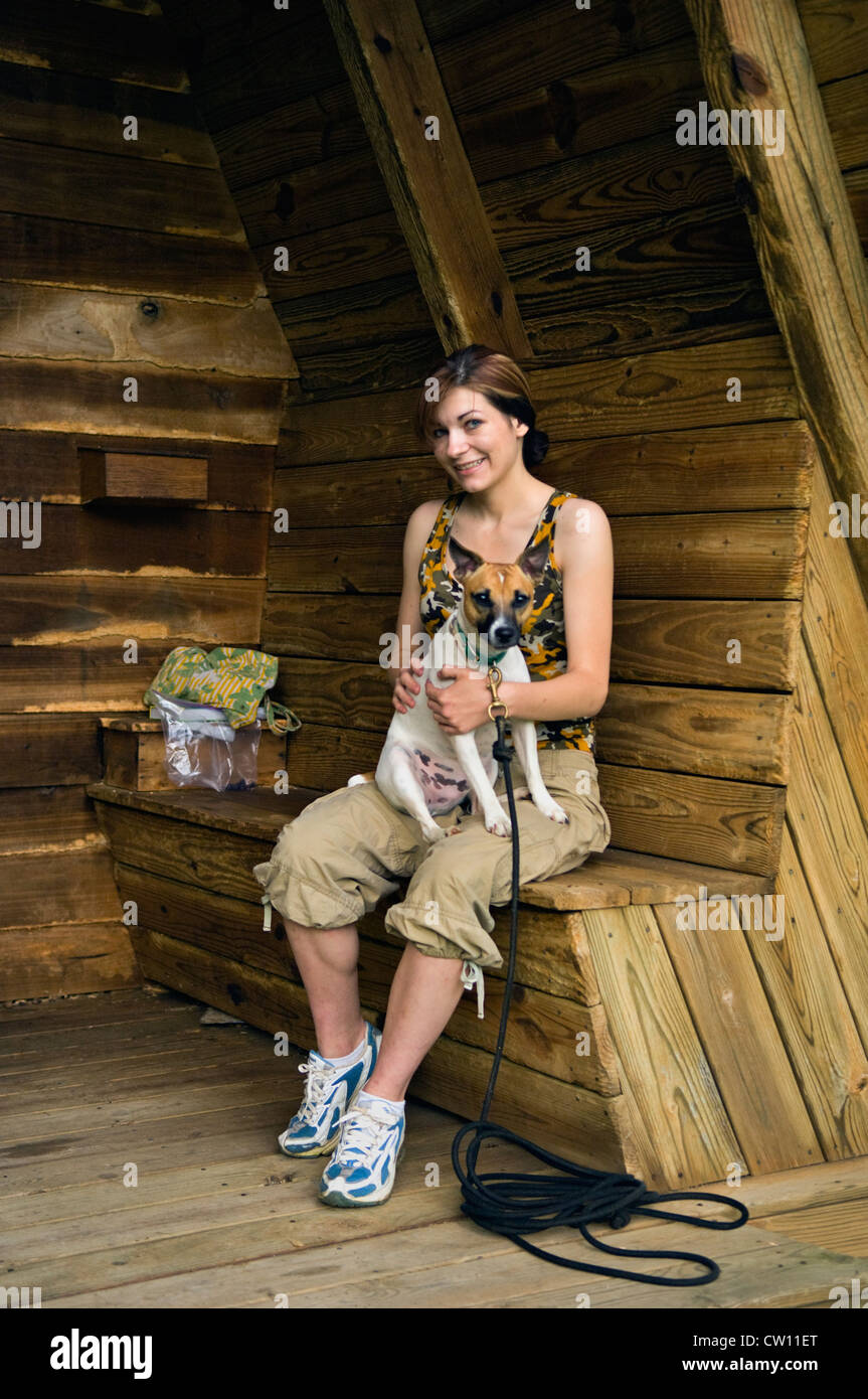 Young Woman Sitting with Jack Russell Terrier in Shelter along Hiking Trail at Mount Saint Francis in Floyd County, - Stock Image