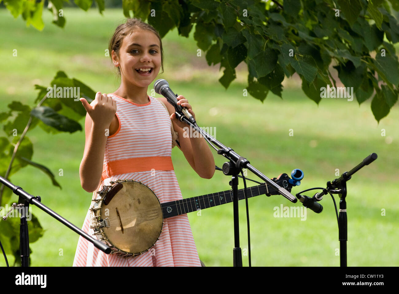 Young Girl Playing Banjo with Barefoot Best Friends Performing at the Kentucky Music Weekend at Iroquois Park in - Stock Image