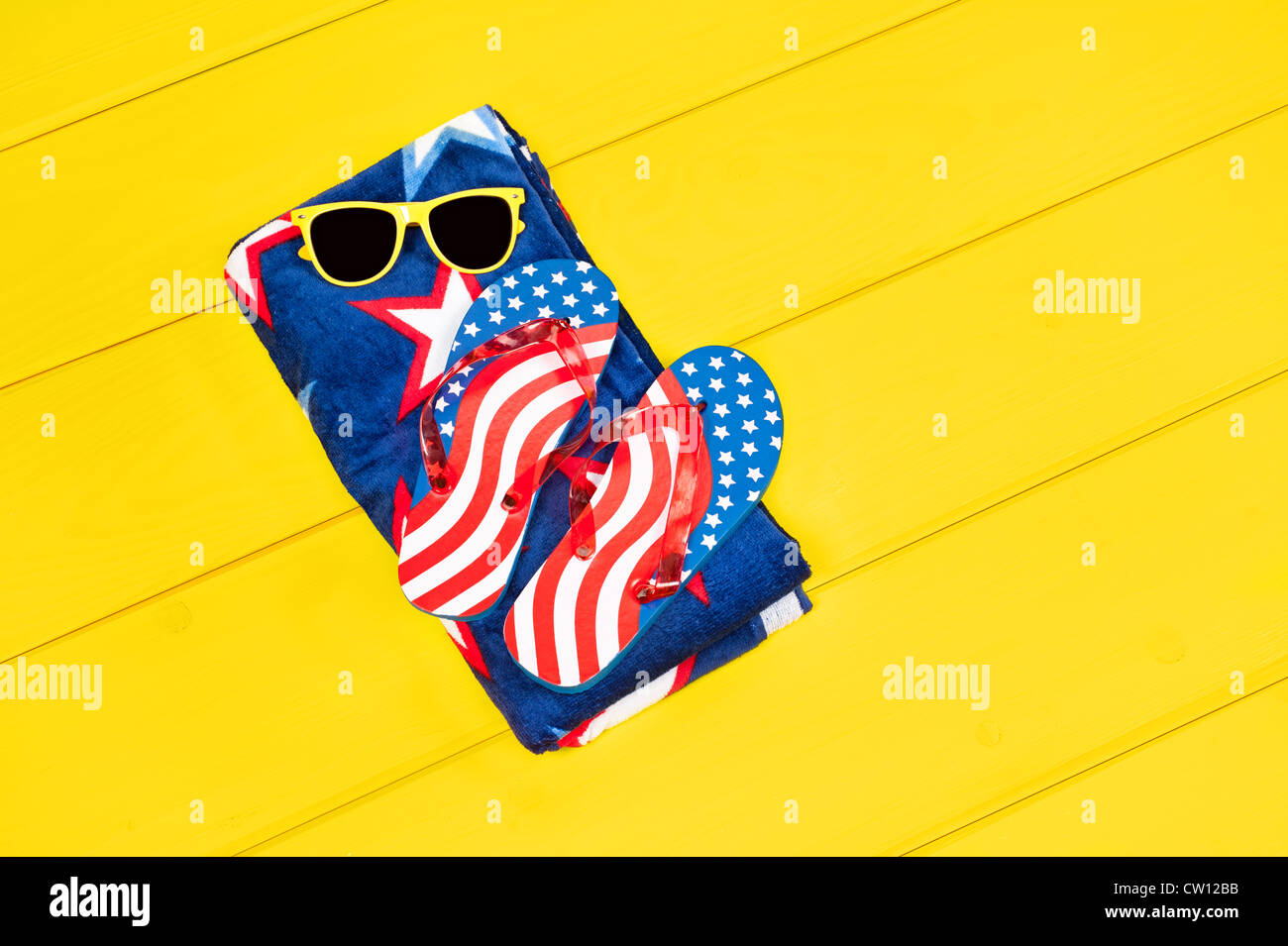 Fourth of July flip flops and patriotic towel resting on a yellow pool deck. Plenty of room for copy. - Stock Image