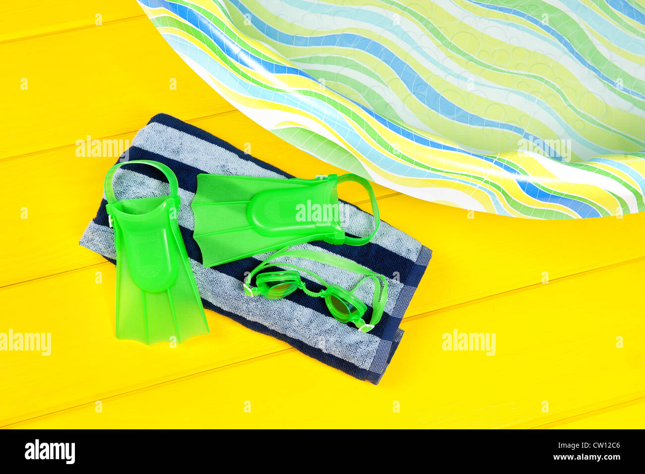 Swim flippers and eye goggles on a beach towel next to a plastic youth swimming pool. Stock Photo