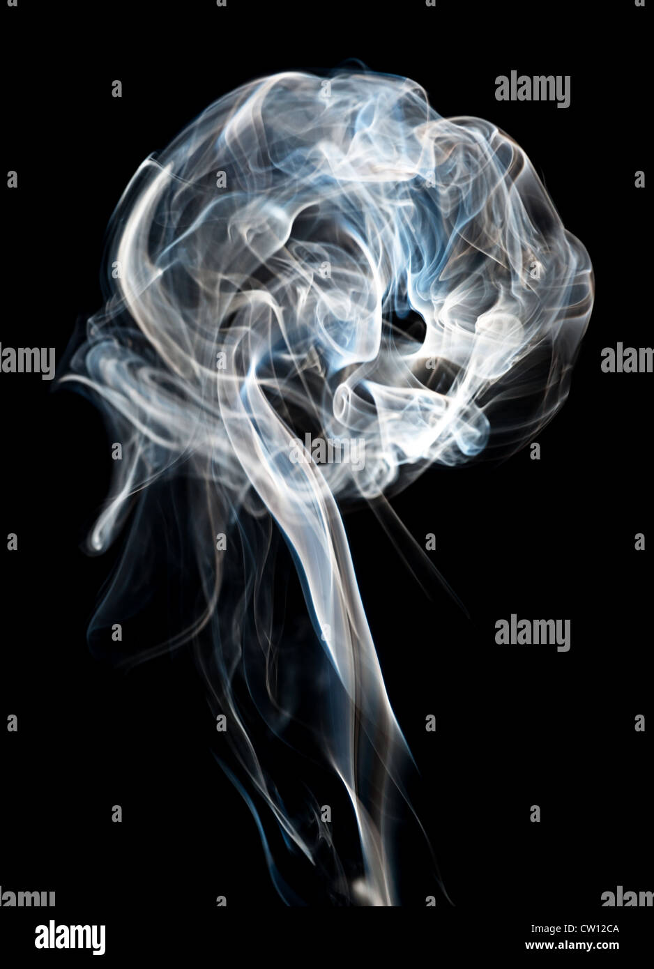 A plume of cigarette smoke against a black background. - Stock Image