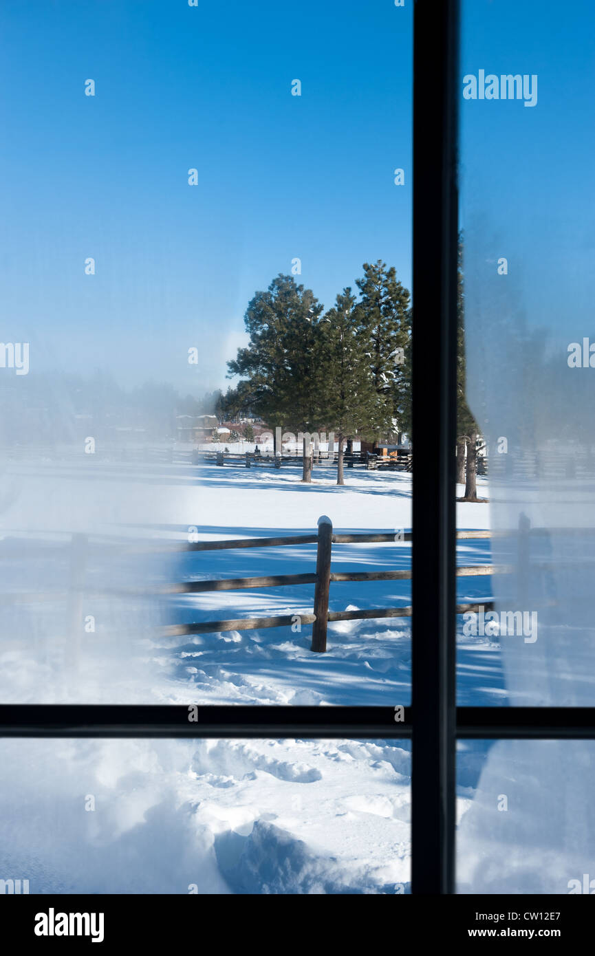 A view out a cabin window with condensation overlooking a snowy mountain landscape - Stock Image