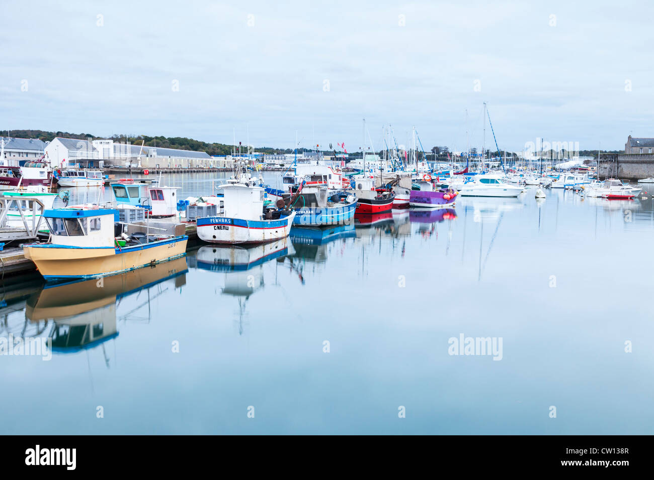Fishing boats in the harbour at Concarneau, Brittany, France, and the fish auction house on the left. - Stock Image