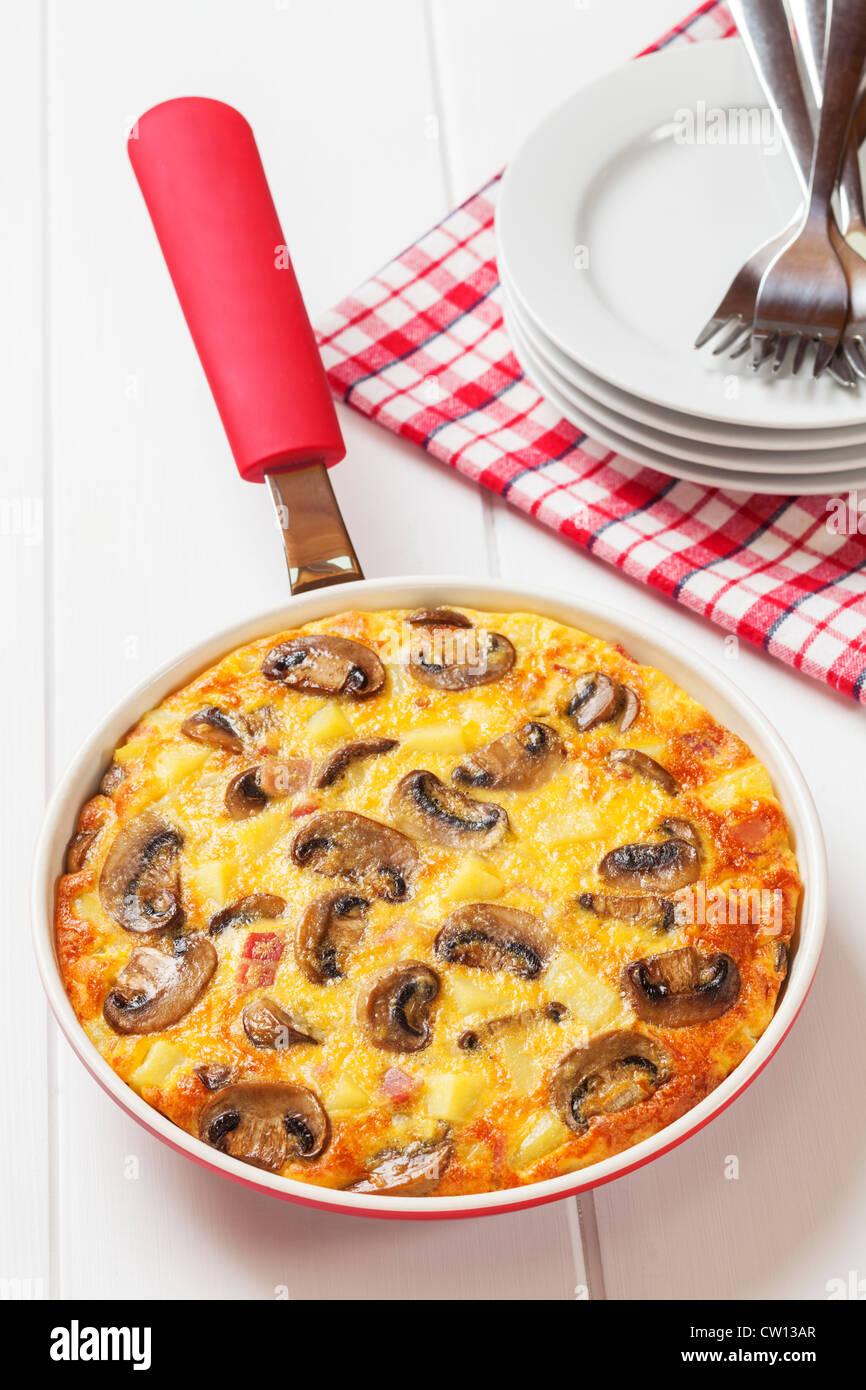 Frittata with bacon, potato, mushroom and onion. - Stock Image
